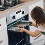 kid putting cookies in oven