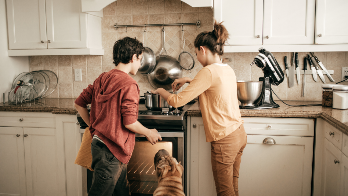 two kids baking with dog at their side