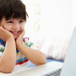 kid smiling in front of laptop