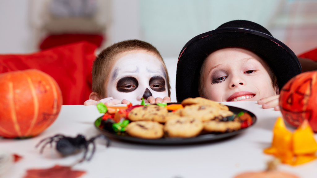 kids in halloween costumes looking at cookies